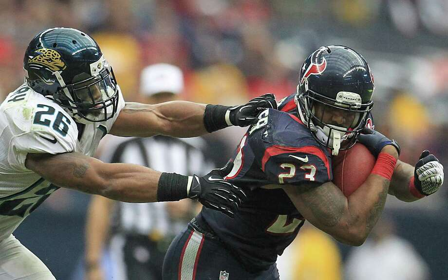 Texans running back Arian Foster (23) runs as he tries to avoid getting tackled by Jaguars strong safety Dawan Landry (26) during the fourth quarter. Photo: Karen Warren, Houston Chronicle / © 2012  Houston Chronicle