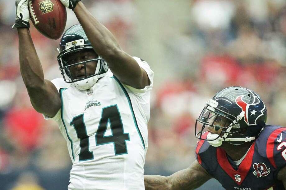 Jaguars wide receiver Justin Blackmon (14) makes a catch as Texans cornerback Kareem Jackson (25) defends during the third quarter. Photo: Nick De La Torre, Houston Chronicle / © 2012  Houston Chronicle