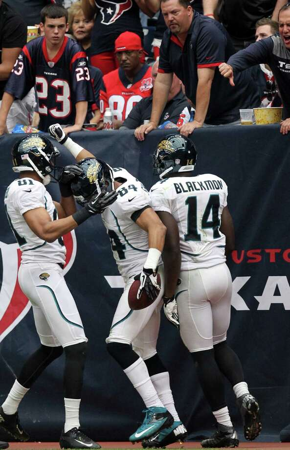 Texans fans look on as Jacksonville Jaguars wide receiver Cecil Shorts (84) celebrates with  Laurent Robinson (81) and Justin Blackmon (14) after scoring on a 67-yard touchdown reception during the second quarter. Photo: Nick De La Torre, Houston Chronicle / © 2012  Houston Chronicle