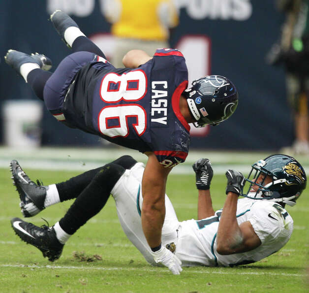 Texans fullback James Casey (86) is upended by Jacksonville cornerback Derek Cox (21) during the fir