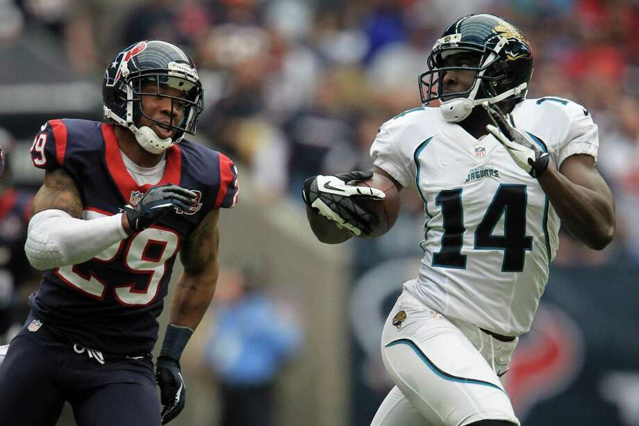 Jaguars wide receiver Justin Blackmon (14) runs away from Texans strong safety Glover Quin (29) during the first quarter. Photo: Karen Warren, Houston Chronicle / © 2012  Houston Chronicle