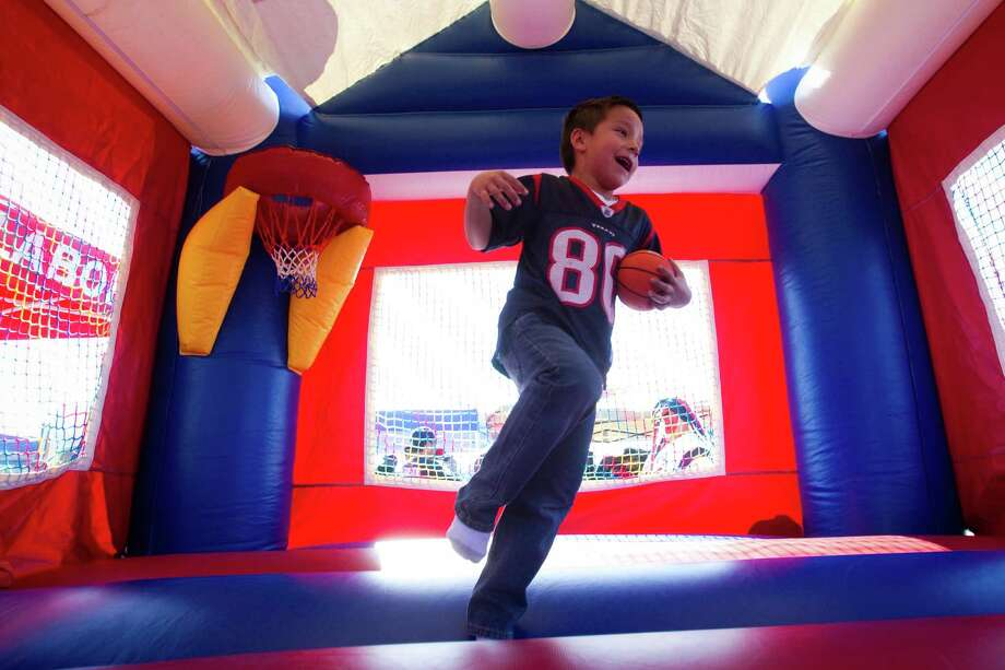 Texans fan Tristen Flores plays in a moonwalk before the Texans game against the Jacksonville Jaguars at Reliant Stadium. Photo: Brett Coomer, Houston Chronicle / © 2012  Houston Chronicle