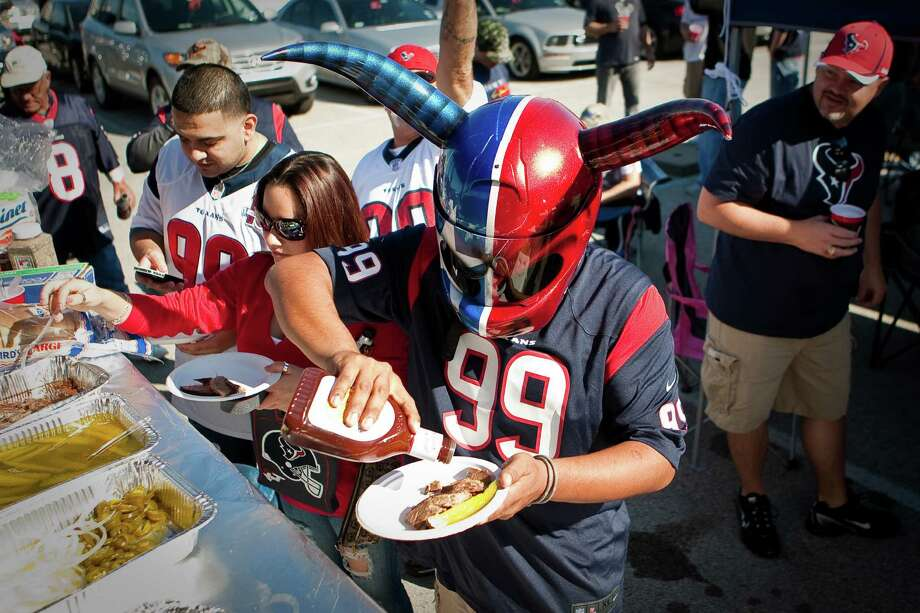 J.R. Zelaya, of Houston, puts ketchup on his brisket as he visits the Ameri-Tex tail gate crew before the game. Photo: Nick De La Torre, Houston Chronicle / © 2012  Houston Chronicle