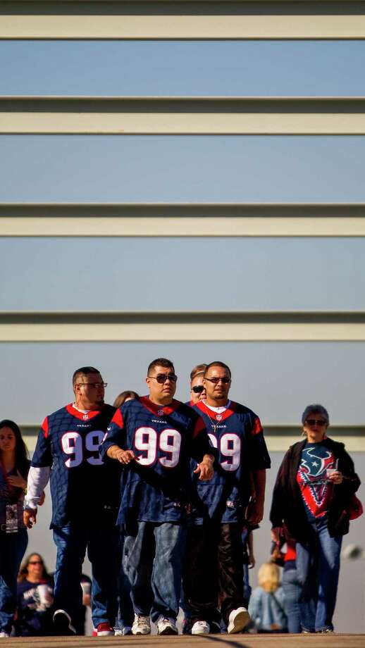 Luis Mendoza, of Houston, center, and his friends wear J.J. Watt jerseys as they cross one of the bridges that connect the parking lot to Reliant Stadium. Photo: Nick De La Torre, Houston Chronicle / © 2012  Houston Chronicle