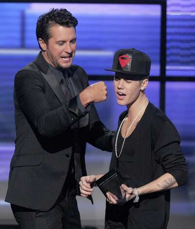 (L-R) Singer Justin Bieber accepts the award for Favorite Pop/Rock Album from presenter Luke Bryan onstage during the 40th American Music Awards held at Nokia Theatre L.A. Live on November 18, 2012 in Los Angeles, California.  (Photo by Kevin Winter/Getty Images) Photo: Kevin Winter, Getty Images / 2012 Getty Images