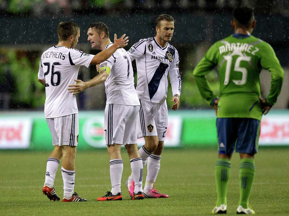 Seattle Sounders' Alvaro Fernandez (15) looks on as Los Angeles Galaxy's Michael Stephens, left, Robbie Keane, second from left, and David Beckham, second from right, celebrate winning the MLS Western Conference championship soccer match, Sunday, Nov. 18, 2012, in Seattle. The Sounders and Galaxy finished Sunday's leg with a score of Sounders 2, Galaxy 1, which gave the Galaxy a 4-2 total in the two-match aggregate championship. The Galaxy will now face the Houston Dynamo in the MLS Cup on Dec. 1. (AP Photo/Ted S. Warren) Photo: Associated Press