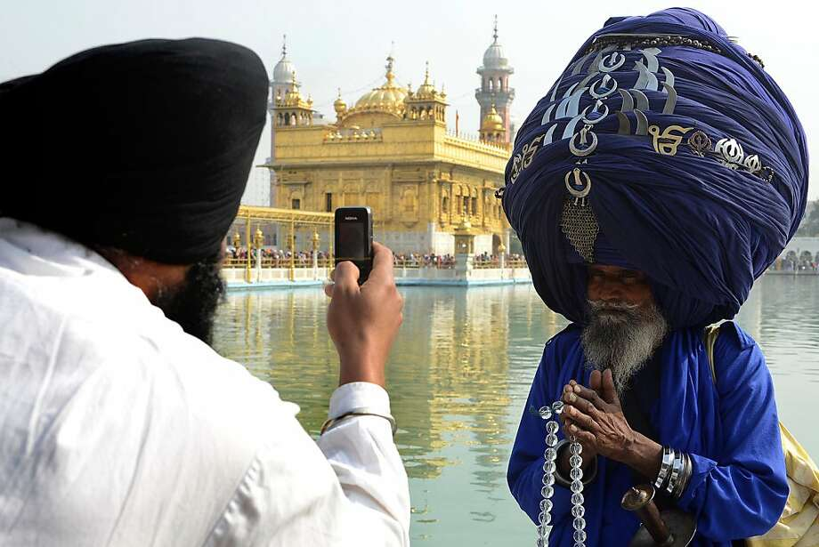 An Indian Sikh devotee takes photographs on his mobile phone of member of the Sikh Nihang Army - traditional Sikh religious warriors - Baba 'Jagir' Singh wearing a turban of some 300 metres in length at the Sikh Shrine, the Golden Temple in Amritsar on November 18, 2012 on the occasion of Martyrdom Day - Jyoti Jot Divas - of Guru Gobind Singh and Sikh warrior, Shaheed Baba Deep Singh.  Guru Gobind Singh, who was the Tenth and the last of the living Sikh Gurus, initiated the Sikh Khalsa in 1699, passing the Guruship of the Sikhs to the Eleventh and Eternal Guru of the Sikhs, the Guru Granth Sahib. NARINDER NANU/AFP/Getty Images Photo: Narinder Nanu, AFP/Getty Images