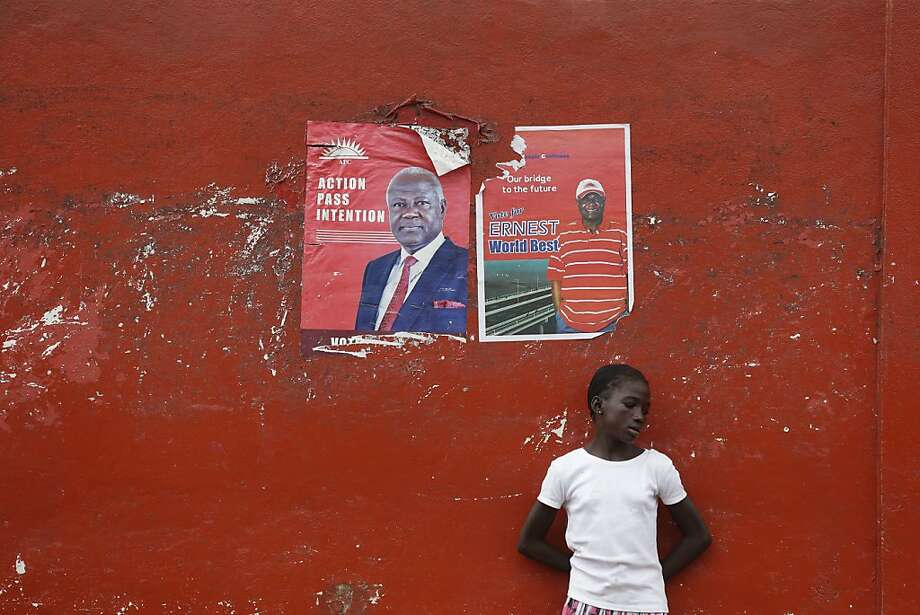 A girl rests against a wall below election posters for incumbent President Ernest Bai Koroma, in Freetown, Sierra Leone, Sunday, Nov. 18, 2012. Sierra Leoneans chose Saturday between keeping an incumbent president who has expanded health care and paved roads or electing an opposition candidate to lead this war-scarred nation still recovering a decade later despite its mineral riches. Election results were still being compiled on Sunday. (AP Photo/Rebecca Blackwell) Photo: Rebecca Blackwell, Associated Press