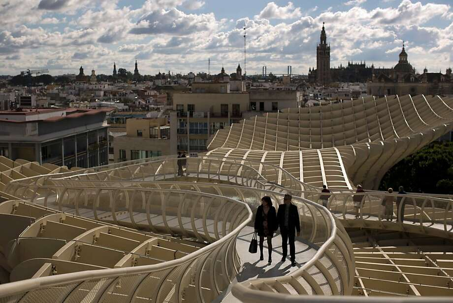 A couple walk along of one the corridors of the Metropol Parasol, overseeing the old city and the Giralda Cathedral of Seville, Spain, Sunday, Nov. 18, 2012. The Metropol Parasol by Jurgen Mayer H. Architects claims to be the world's largest wooden structure. (AP Photo/Emilio Morenatti) Photo: Emilio Morenatti, Associated Press