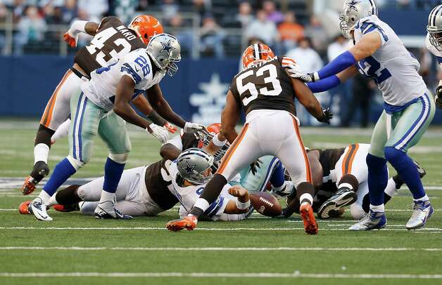 Dallas Cowboys quarterback Tony Romo (9) fumbles as Cleveland Browns linebacker Craig Robertson (53) looks to recover the ball during the second half of an NFL football game Sunday, Nov. 18, 2012 in Arlington, Texas. (AP Photo/Sharon Ellman) Photo: Sharon Ellman, Associated Press / FR170032 AP