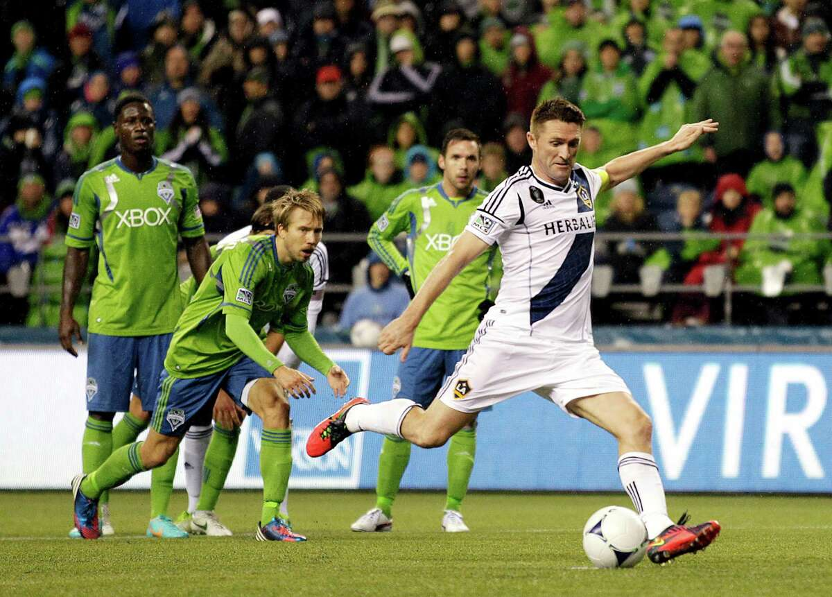 Los Angeles Galaxy's Robbie Keane right, kicks a penalty kick for a goal after Seattle Sounders' Adam Johansson, second from left, was called for a hand ball in the second half of the second leg of the MLS Western Conference championship, Sunday in Seattle. The Sounders and Galaxy finished Sunday's leg with a score of Sounders 2, Galaxy 1, which gave the Galaxy a 4-2 win over the Sounders in the two-match aggregate championship. The Galaxy will now face the Houston Dynamo in the MLS Cup on Dec. 1, 2012. (AP Photo/Ted S. Warren)