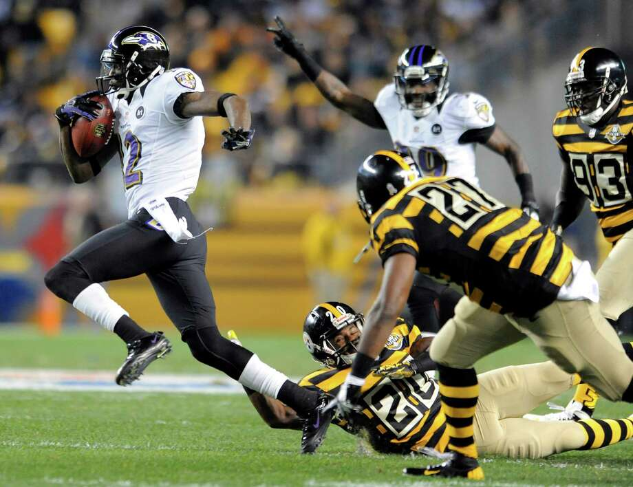 The Ravens' Jacoby Jones heads for the end zone as he leaves a tangled mess of striped Steelers in his wake on a 63-yard punt return for a touchdown Sunday night. It was his third return TD this season. Photo: Lloyd Fox, MBR / Baltimore Sun