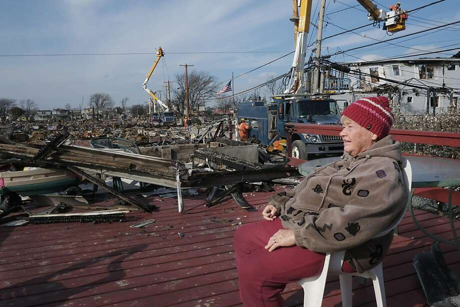 Helen Graham sits on the porch of her fire-damaged home while waiting to meet an insurance adjuster, Sunday, Nov. 18, 2012 in the Breezy Point section of the Queens borough of New York. More than 100 homes were destroyed by fire in the oceanside community during Superstorm Sandy. (AP Photo/Mark Lennihan) Photo: Mark Lennihan, Associated Press