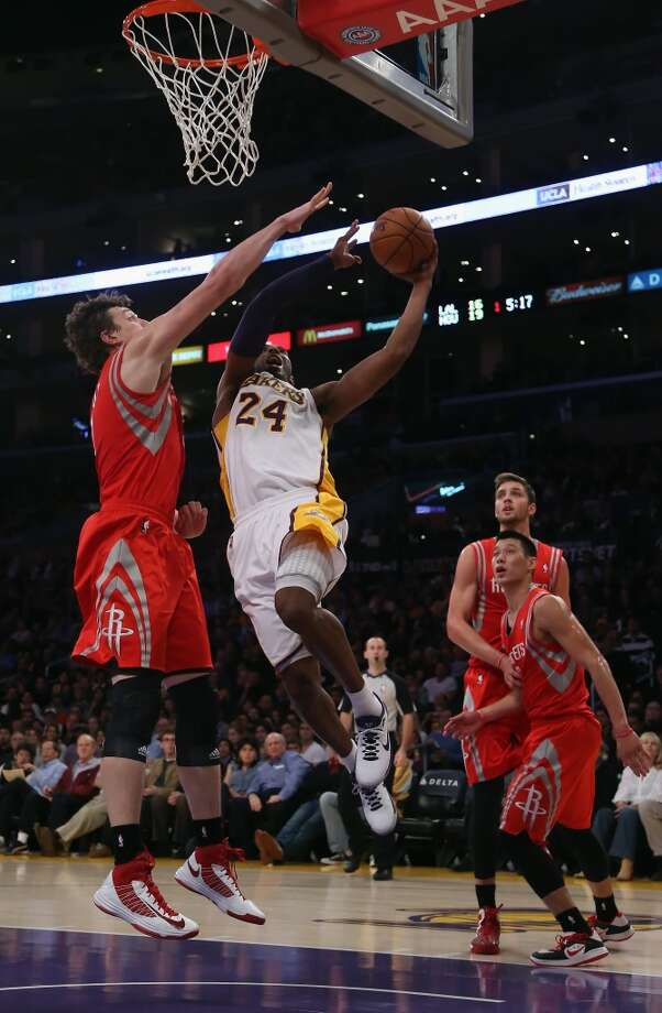 Kobe Bryant drives past Omer Asik of the Rockets for a lay up in the first half.  (Jeff Gross / Getty Images)