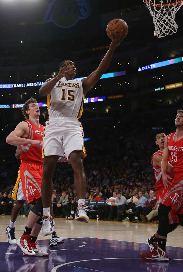 Metta World Peace #15 of the Lakers drives past Omer Asik #3 of the Rockets for a lay up in the first half.  (Jeff Gross / Getty Images)