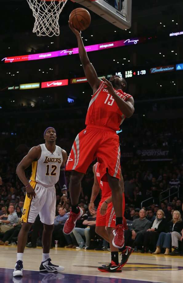 Toney Douglas of the Rockets drives to the basket past Dwight Howard. (Jeff Gross / Getty Images)
