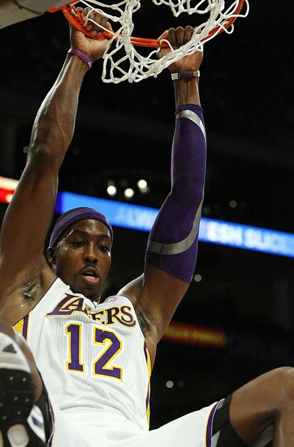 Lakers center Dwight Howard hangs on the rim after a slam dunk. (Luis Sinco / McClatchy-Tribune News Service)