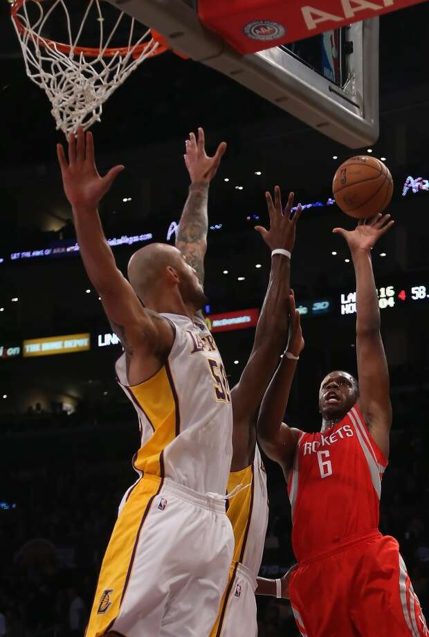 Terrence Jones of the Rockets drives to the basket while defended by Robert Sacre #50 of the Lakers in the second half.  (Jeff Gross / Getty Images)
