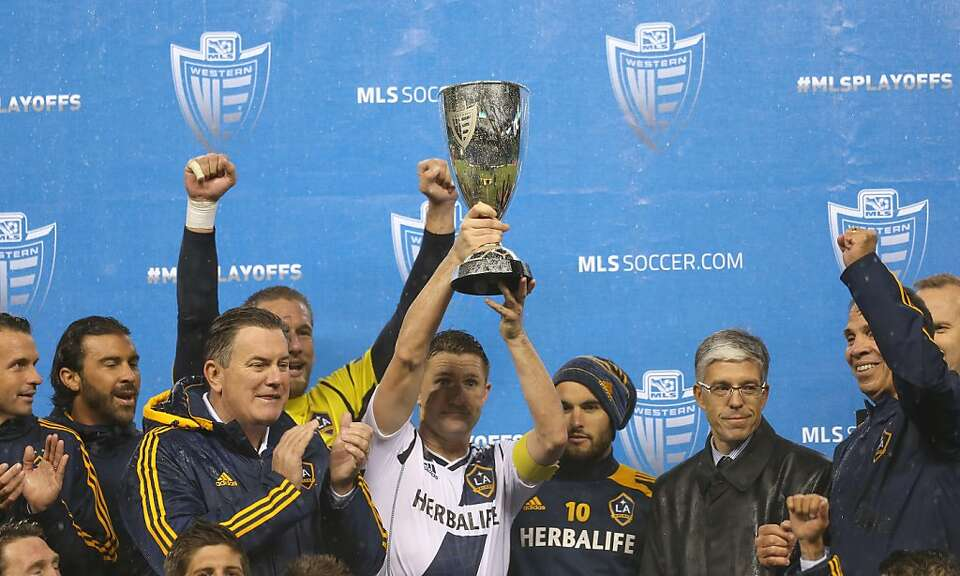 L.A.'s Robbie Keane hoists the Western Conference championship hardware in Seattle.
