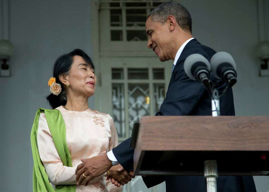 U.S. President Barack Obama and Myanmar opposition leader Aung San Suu Kyi shake hands after speaking to the media at her residence in Yangon, Myanmar, Monday, Nov. 19, 2012. Obama who touched down Monday morning, becoming the first U.S. president to visit the Asian nation also known as Burma, said his historic visit to Myanmar marks the next step in a new chapter between the two countries. (AP Photo/Carolyn Kaster) Photo: Carolyn Kaster