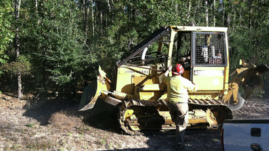 Porter firefighters call in reinforcements, including a bulldozer from the Texas Forest Service, to contain an eight-acre forest fire Sunday. (Scott Engle / Montgomery County Police Reporter) Photo: Montgomery County Police Reporter