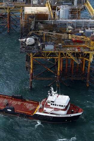 A supply vessel moves near an oil platform damaged by an explosion and fire, Friday, Nov. 16, 2012, in the Gulf of Mexico about 25 miles southeast of Grand Isle, La. Four people were transported to a hospital with critical burns and two were missing.