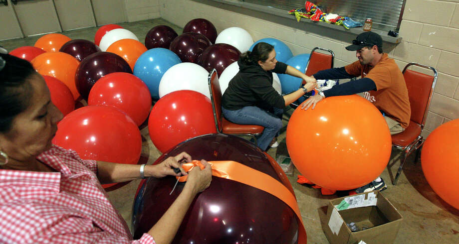 Celia Ellis, Jennifer Roth and Micah Teich, work to inflate approximately 150 3-foot balloons, Nov. 26, 2008, for the 29th annual Raul Jimenez Thanksgiving Dinner, at the Convention Center. Photo: GLORIA FERNIZ, SAN ANTONIO EXPRESS-NEWS / gferniz@express-news.net