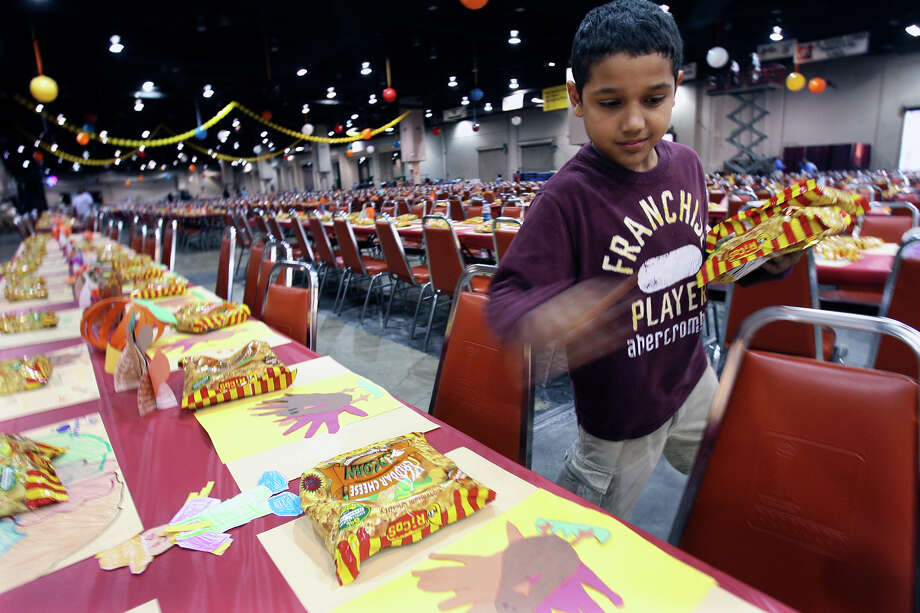 12-year-old A.J. Davis places bags of popcorn as he and other volunteer workers prepare tables for the Raul Jimenez Thanksgiving meal at the Convention Center, Nov. 26, 2008. Photo: TOM REEL, SAN ANTONIO EXPRESS-NEWS / treel@express-news.net