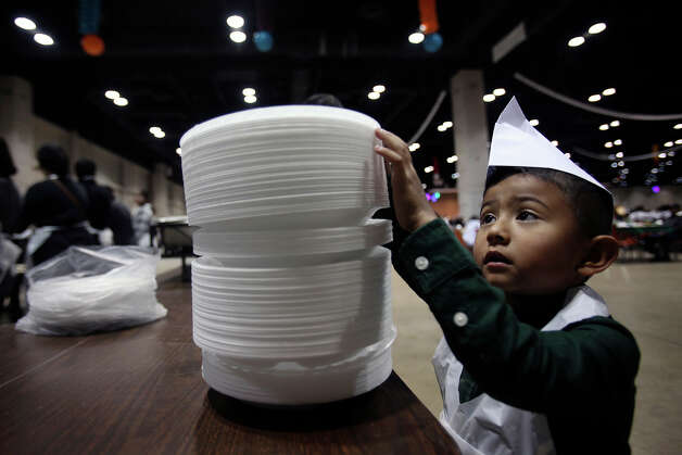 Alfredo Calderon III, 4, tries to separate a pile of plates to a more manageable size as he takes on the task of starting the dinner plate assembly line so that servers can take meals to tables at the 30th Annual Raul Jimenez Thanksgiving Dinner, at the Convention Center, Nov. 26, 2009. Photo: Shaminder Dulai, San Antonio Express-News / sdulai@express-news.net