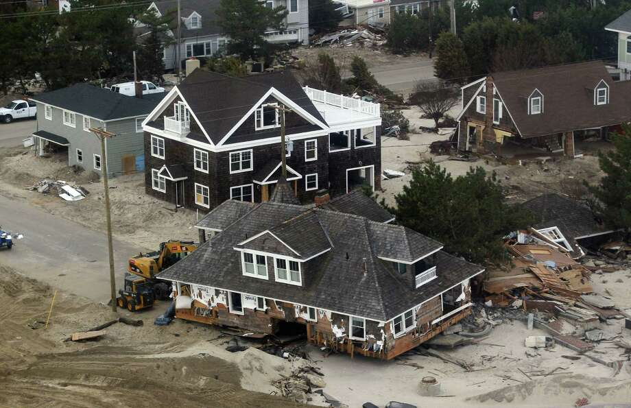 A house in Mantoloking, N.J. is knocked off its foundation and others destroyed in areas damaged by Superstorm Sandy Sunday, Nov. 18, 2012. Vice President Joe Biden was on another helicopter surveying the same damage. Photo: Rich Schultz, AP / FR27227 AP