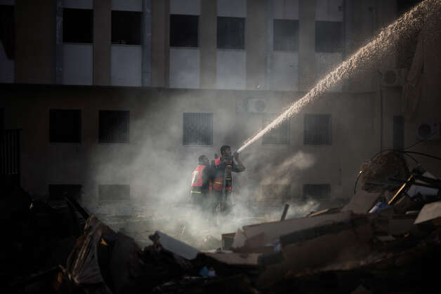 Palestinian firefighters try to extinguish a fire at the Civilian Affairs branch of the Ministry of Interior following an Israeli air raid in Gaza City on November 16, 2012. Israel was condemned by much of the Arab world while securing Western backing and pressing its biggest air assault on Gaza for years amid a wave of Palestinian short-range rocket fire. Photo: MARCO LONGARI, AFP/Getty Images / 2012 AFP