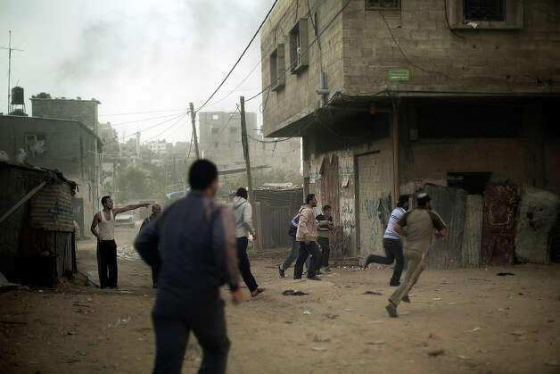Palestinians run for cover after an Israeli airstrike hit the northern Gaza City on November 16, 2012. Gaza militants targeted Tel Aviv on November 16, with another rocket, defying Israeli warnings of a possible ground assault to follow its aerial bombardment of the Hamas-run strip. Photo: MARCO LONGARI, AFP/Getty Images / 2012 AFP