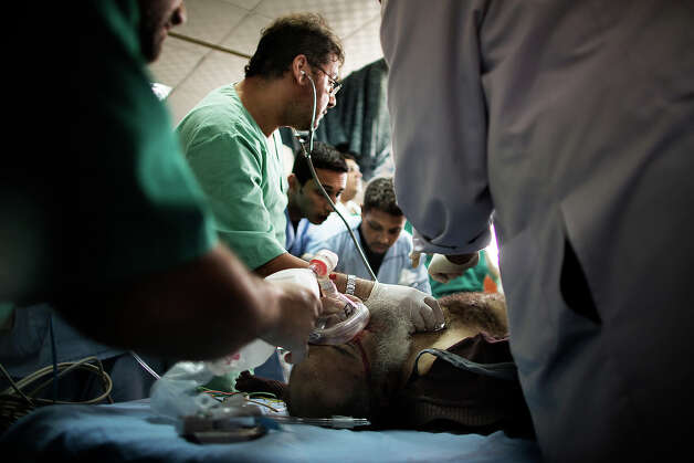 Palestinian medical workers treat a badly wounded Palestinian at al-Shifa hospital in Gaza City on November 16, 2012. A rocket fired by militants in the Gaza Strip hit a West Bank settlement bloc just south of Jerusalem, Israeli police said, with the army saying it had called no injuries or damages. Photo: MARCO LONGARI, AFP/Getty Images / 2012 AFP