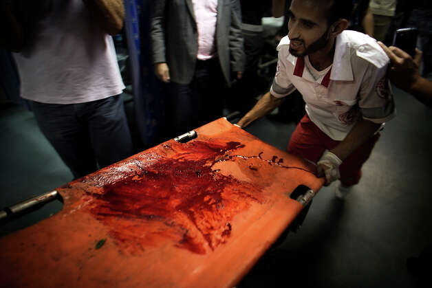 A Palestinian medical worker pushes a bloody stretcher at al-Shifa hospital in Gaza City on November 16, 2012. A rocket fired by militants in the Gaza Strip hit a West Bank settlement bloc just south of Jerusalem, Israeli police said, with the army saying it had called no injuries or damages. Photo: MARCO LONGARI, AFP/Getty Images / 2012 AFP