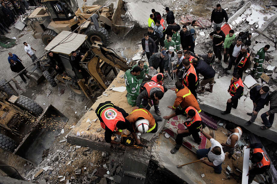 Palestinian firefighters and rescue personnel work at a blast site following an Israeli air raid in Gaza City on November 17, 2012.  Israeli air strikes hit the cabinet headquarters of Gaza's Hamas government, the group said early on November 17, with eyewitnesses reporting extensive damage to the building. Photo: MARCO LONGARI, AFP/Getty Images / 2012 AFP