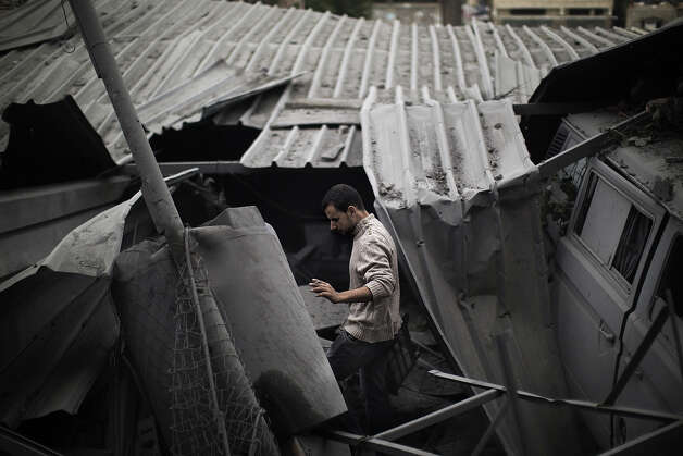 A Palestinian man inspects damages at the site of an Israeli air raid in Gaza City on November 17, 2012. Israeli air strikes hit the cabinet headquarters of Gaza's Hamas government after militants fired rockets at Jerusalem and Tel Aviv as Israel called up thousands more reservists in readiness for a potential ground war. Photo: MARCO LONGARI, AFP/Getty Images / 2012 AFP