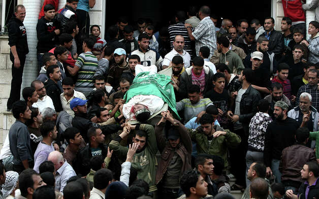 Palestinian mourners carry the body of a man during the funeral of people killed in Israeli air strikes in Maghazi refugee camp in central Gaza Strip on November 17, 2012. Israeli strikes on Gaza killed at least eight Palestinians and destroyed the Hamas government headquarters as Israel called up thousands more reservists for a possible ground war. Photo: MAHMUD HAMS, AFP/Getty Images / 2012 AFP