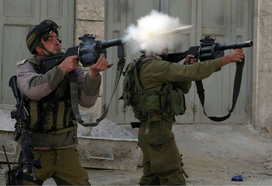 Israeli soldiers fire tear gas towards stone throwers demonstrating against the Israeli military offensive on the Gaza Strip in the village of Beit Omar, north of the West Bank town of Hebron, on November 17, 2012. Egypt and Turkey put the onus on Israel to end the fighting around Gaza as Turkish Prime Minister Recep Tayyip Erdogan visited Cairo a day after Washington urged the two governments to pressure the Palestinians. Photo: HAZEM BADER, AFP/Getty Images / 2012 AFP