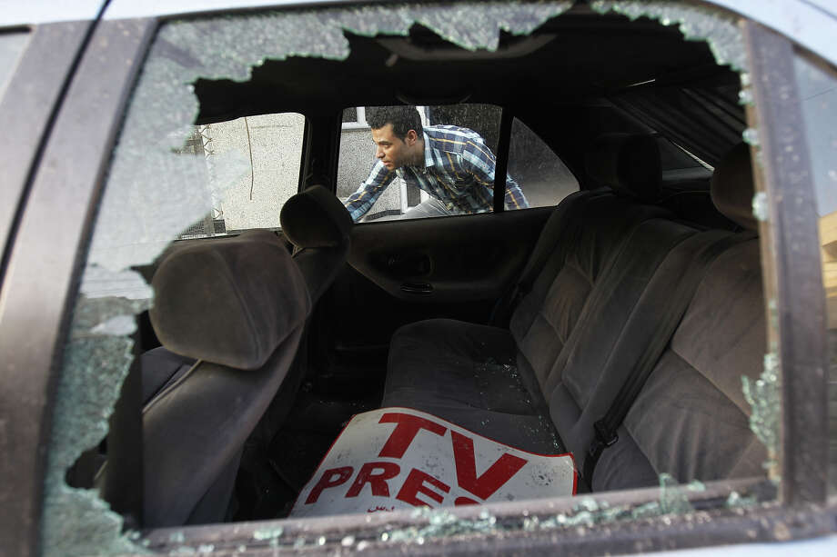 A Palestinian journalist inspects his work car in Gaza City on November 18, 2012. An Israeli air strike hit a Gaza City media building on November 18, injuring at least six journalists, as a separate raid in northern Gaza killed two people, Palestinian medical sources said. Photo: MOHAMMED ABED, AFP/Getty Images / 2012 AFP