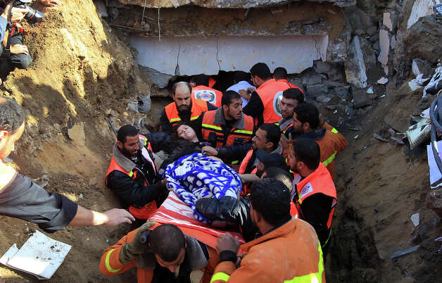 "Palestinian civil defense staff carry a survivor on a stretcher after she was pulled out from under the rubble of a destroyed house following an Israeli air strike on Gaza City on November 18, 2012. Fresh Israeli air strikes hit a Gaza City media centre and homes in northern Gaza in the early morning, as the death toll mounted, despite suggestions from Egypt's President Mohamed Morsi that there could be a ""ceasefire soon."" Photo: MAHMUD HAMS, AFP/Getty Images / 2012 AFP"