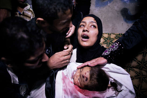 The mother of 10-month-old Palestinian girl, Hanen Tafesh, killed the day before in an Israeli air strike, is comforted by her husband and relatives as she mourns before her funeral in Gaza City, on November 16, 2012. Israeli warplanes carried out multiple new air strikes on the Palestinian territory, including several hits on Gaza City, the third day of an intensive campaign which the military has said is aimed at stamping out rocket fire on southern Israel. Photo: MARCO LONGARI, AFP/Getty Images / 2012 AFP