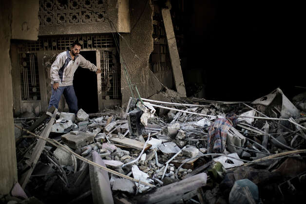 "A Palestinian man inspects his damaged house following Israeli air strikes the village of Beit Lahia in the northern Gaza Strip on November 18, 2012. Israeli war planes hit a Gaza City media centre and homes in northern Gaza in the early morning, as the death toll mounted, despite suggestions from Egypt's President Mohamed Morsi that there could be a ""ceasefire soon."" Photo: MARCO LONGARI, AFP/Getty Images / 2012 AFP"