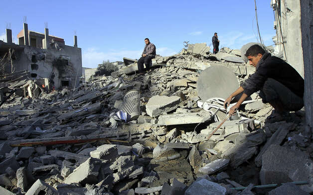 "Palestinians look at their destroyed homes following Israeli air strikes on the southern Gaza Strip town of Rafah on November 18, 2012. Israeli war planes hit a Gaza City media centre and homes in northern Gaza in the early morning, as the death toll mounted, despite suggestions from Egypt's President Mohamed Morsi that there could be a ""ceasefire soon."" Photo: SAID KHATIB, AFP/Getty Images / 2012 AFP"