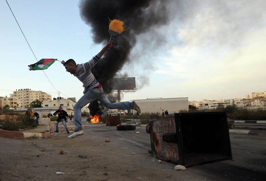 A Palestinian student from Birzeit University jumps over a dumpster during clashes with Israeli soldiers for the second consecutive day as they protest against the ongoing Israeli offensive on the Gaza Strip in the West Bank town of Betunia on November 18, 2012. Israel's Foreign Minister Avigdor Lieberman said that Israel would not negotiate a truce with Gaza Strip's Hamas rulers as long as rocket fire continues from the Palestinian enclave. Photo: ABBAS MOMANI, AFP/Getty Images / 2012 AFP