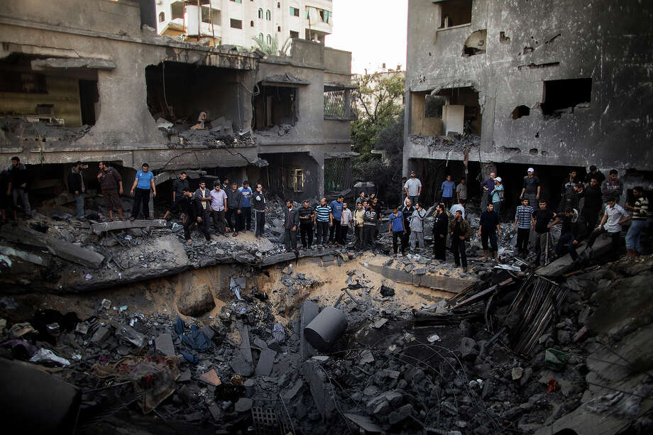 Palestinian men gather around a crater caused by an Israeli air strike on the al-Dallu family's home in Gaza City on November 18, 2012. Israeli air strikes killed at least 18 Palestinians in the bloodiest day so far of its massive air campaign on the Gaza Strip, as diplomatic efforts to broker a truce intensified. Photo: MARCO LONGARI, AFP/Getty Images / 2012 AFP