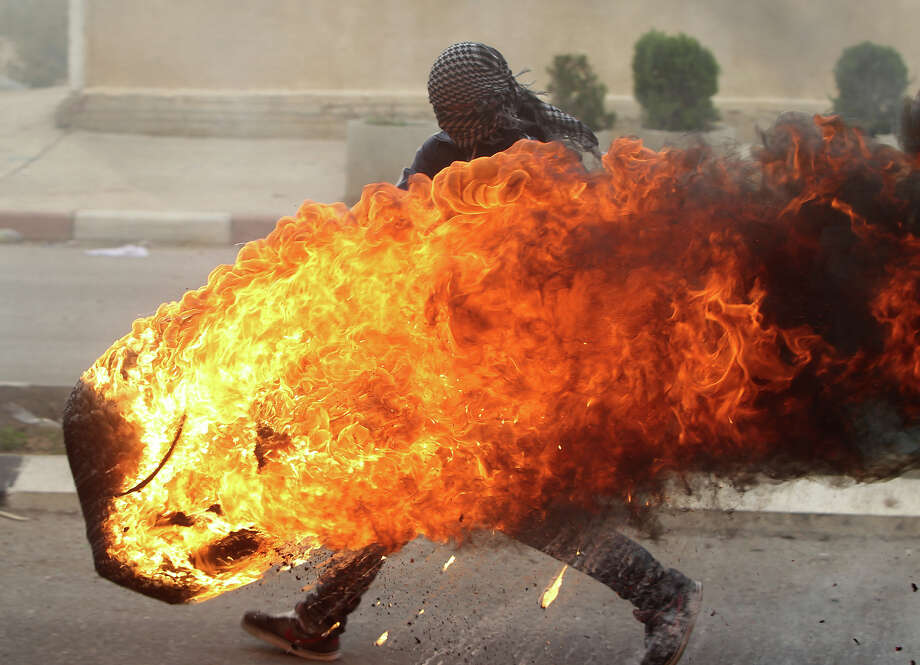A Palestinian student from Birzeit University pushes a burning tire during clashes with Israeli soldiers for the second consecutive day as they protest against the ongoing Israeli offensive on the Gaza Strip in the West Bank town of Betunia on November 18, 2012. Israel's Foreign Minister Avigdor Lieberman said that Israel would not negotiate a truce with Gaza Strip's Hamas rulers as long as rocket fire continues from the Palestinian enclave. Photo: ABBAS MOMANI, AFP/Getty Images / 2012 AFP