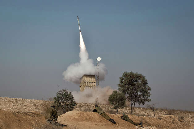 An Israeli soldier lies on the ground as missiles are fired from an Iron Dome anti-missile station on November 15, 2012 near the city of Beer Sheva, Israel. The Iron Dome was activated to intercept incoming rockets launched from Gaza. Three people have reportedly been killed in Israel after a building was hit by a rocket fired from Hamas-ruled Gaza on Thursday, a day after Israeli Defense Forces (IDF) launched a series of aerial strikes on targets in Gaza that killed a top military commander of Hamas. Photo: Ilia Yefimovich, Getty Images / 2012 Getty Images