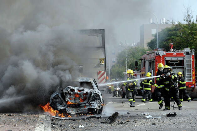 Israeli firemen douse a burning car after a rocket fired by Palestinian militants from the Gaza Strip landed in the southern Israeli city of Ashdod on November 17, 2012. Israeli strikes on Gaza killed at least nine Palestinians and destroyed the Hamas government headquarters as Israel called up thousands more reservists for a possible ground war. Photo: DAVID BUIMOVITCH, AFP/Getty Images / 2012 AFP