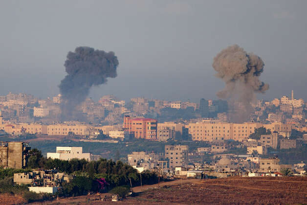 Plumes of smoke rise over Gaza during an Israeli air strike, as seen from Sderot on November 15, 2012 in Israel.  A rocket attack on an apartment building  in Kiryat Malachi, Israel earlier claimed three lives, some 24 hours after the IDF targeted nearly 200 sites in the Gaza Strip, killing Ahmed Jabari, a top military commander of Hamas, in the process. Photo: Uriel Sinai, Getty Images / 2012 Getty Images