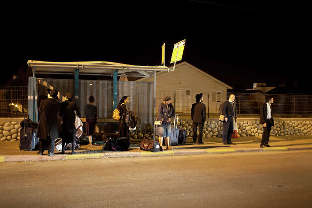 People wait for a bus to leave town on November 14, 2012 in Netivot, Israel. Israel Defense Forces launched aerial attacks on targets in Gaza that killed the top military commander of Hamas. Photo: Uriel Sinai, Getty Images / 2012 Getty Images